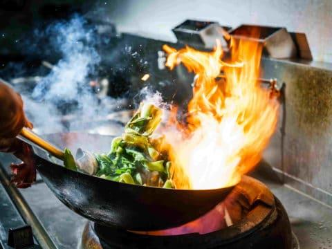 Pfanne mit Gemüse und einer großen Flamme