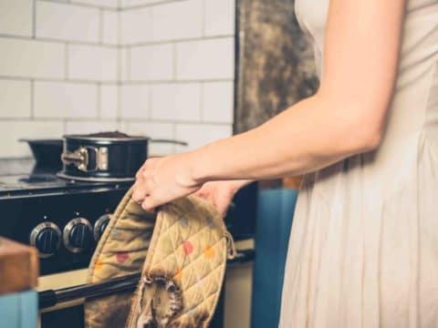 Eine junge Frau steht mit verbrannten Backhandschuhen vorm Ofen.