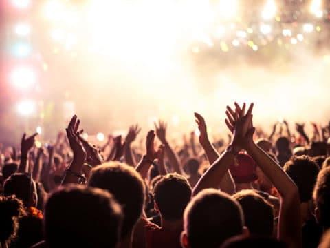 Publikum bei einer Veranstaltung reißt die Hände nach oben.