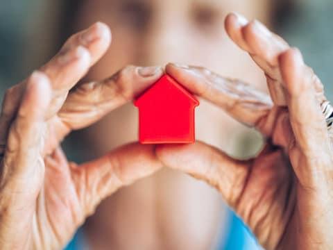 Frau zeigt mit rotem Haus die Bedeutung von Brandschutz für Senioren.
