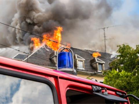 Das Bild zeigt das brennende Dach eines Hauses und ein Feuerwehrauto.
