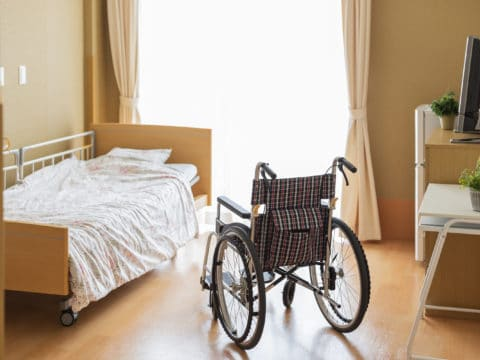 Das Bild zeigt ein Pflegebett und einen Rollstuhl vor einem Fenster in einem hellen Raum.