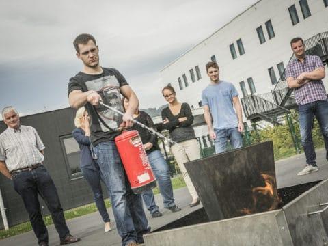 Das Bild zeigt einen Mann, der mit einem Handfeuerlöscher ein kleines Feuer in einem Eimer löscht. Hinter ihm stehen Menschen und schauen zu.