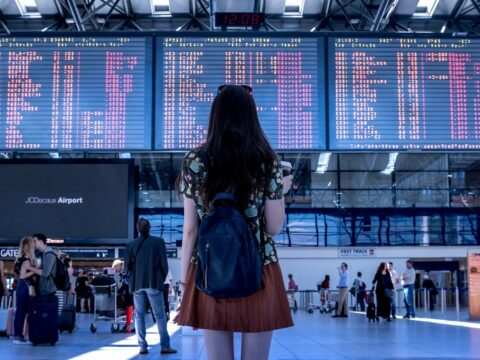 Eine Dame steht am Flughafenterminal und sieht auf eine Anzeige